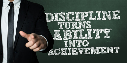 Business man pointing with the text: Discipline Turns Ability Into Achievement